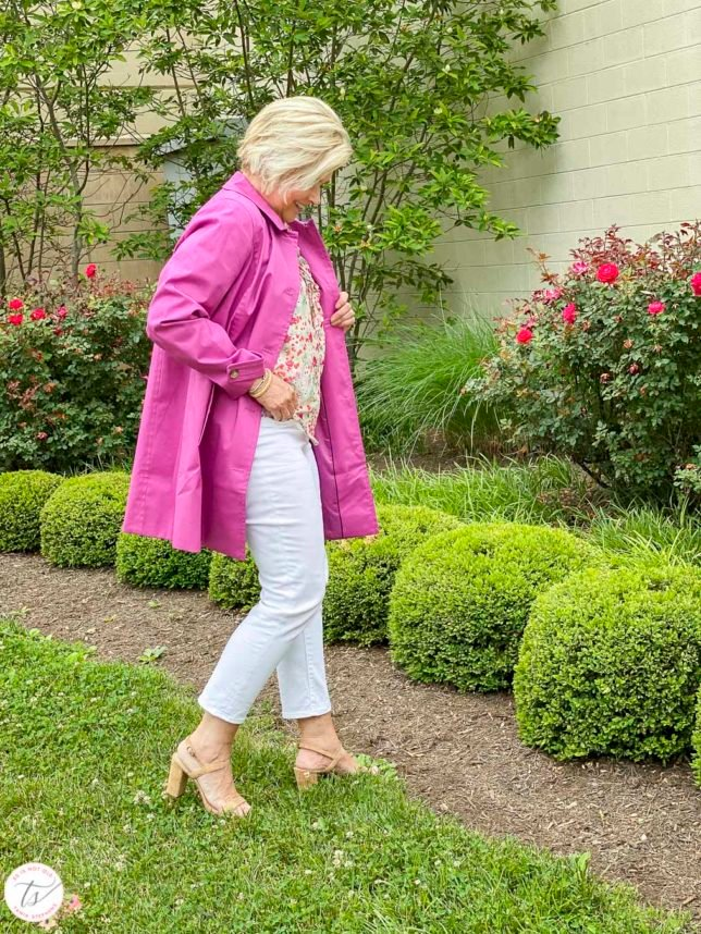 Fashion Blogger 50 Is Not Old is wearing an orchid Mac trench coat with a feminine floral blouse, white crop pants, and cork high heels