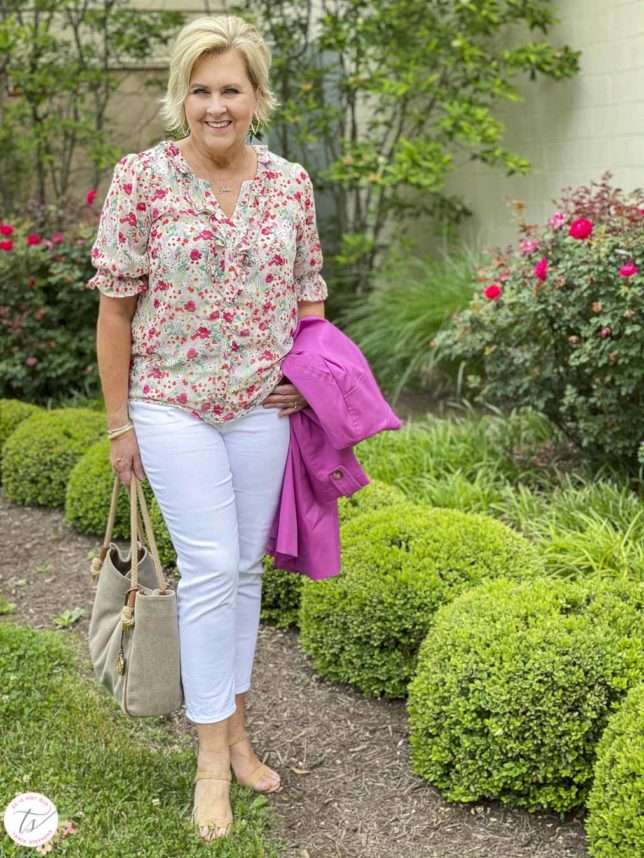 Fashion Blogger 50 Is Not Old is wearing a feminine floral blouse, white crop pants, cork heels, and a Michael Kors handbag