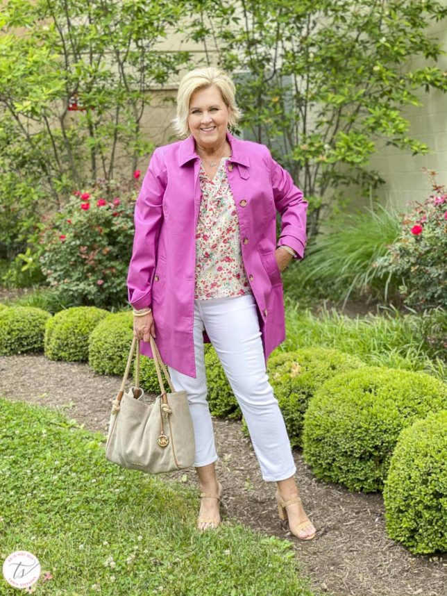 Fashion Blogger 50 Is Not Old is wearing an orchid Mac trench coat with a feminine floral blouse, white crop pants, cork heels, and a Michael Kors handbag