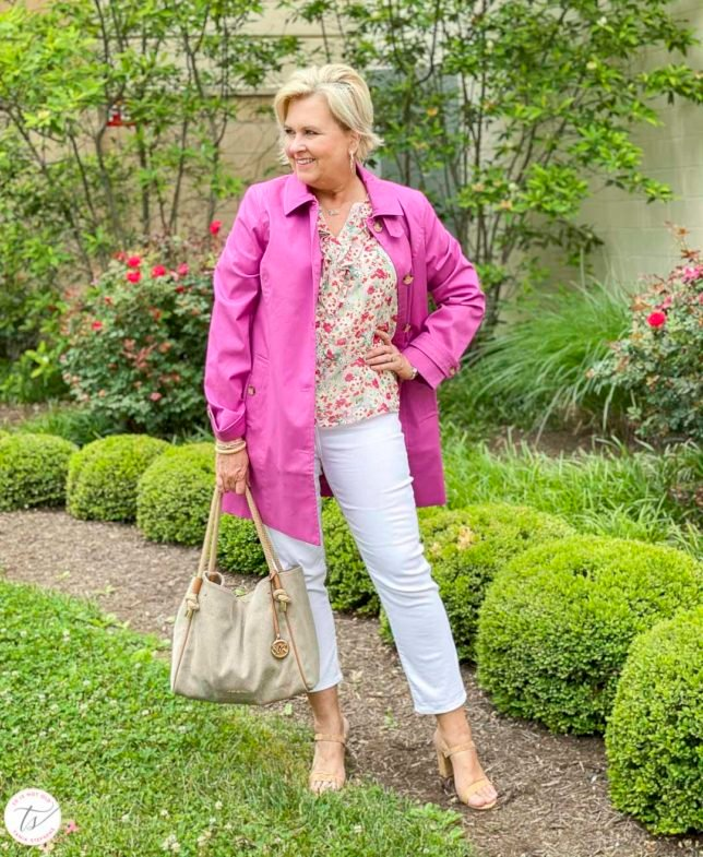 Fashion Blogger 50 Is Not Old is wearing an orchid Mac trench coat with a feminine floral blouse, white crop pants, and cork heels