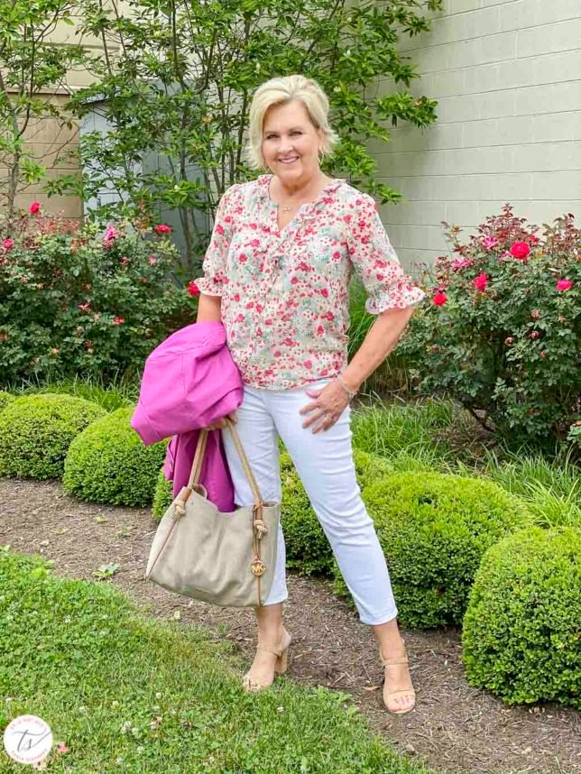 Fashion Blogger 50 Is Not Old is wearing a feminine floral blouse, white crop pants, cork heels, and carrying a orchid trench coat and a Michael Kors handbag
