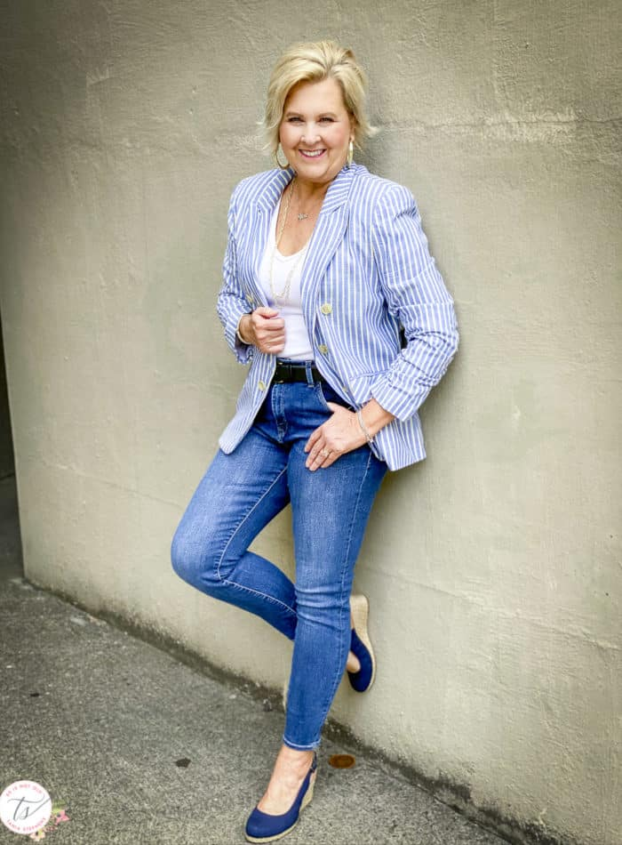 Fashion Blogger 50 Is Not Old is leaning up against a wall while wearing a striped blue and white blazer, a white v-neck bodysuit, skinny jeans, and navy espadrilles