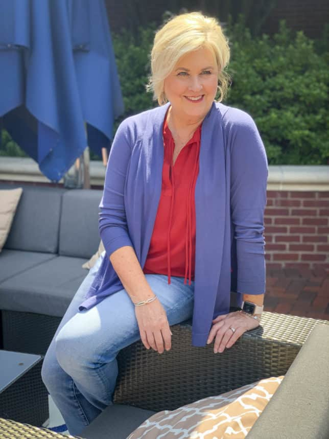 Fashion Blogger 50 Is Not Old is sitting on the arm of a chair in a red top and blue cardigan