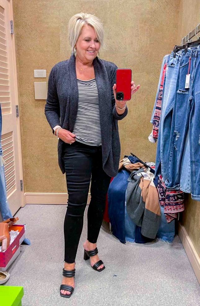 Fashion Blogger 50 Is Not Old is wearing a charcoal circle cardigan, a black and white tee, and black raw hem skinny jeans and black heels from the Nordstrom Anniversary Sale
