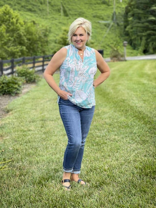 Fashion Blogger 50 Is Not Old is wearing a blue and white print shell with a pair of straight leg ankle jeans and navy sandals from Talbots