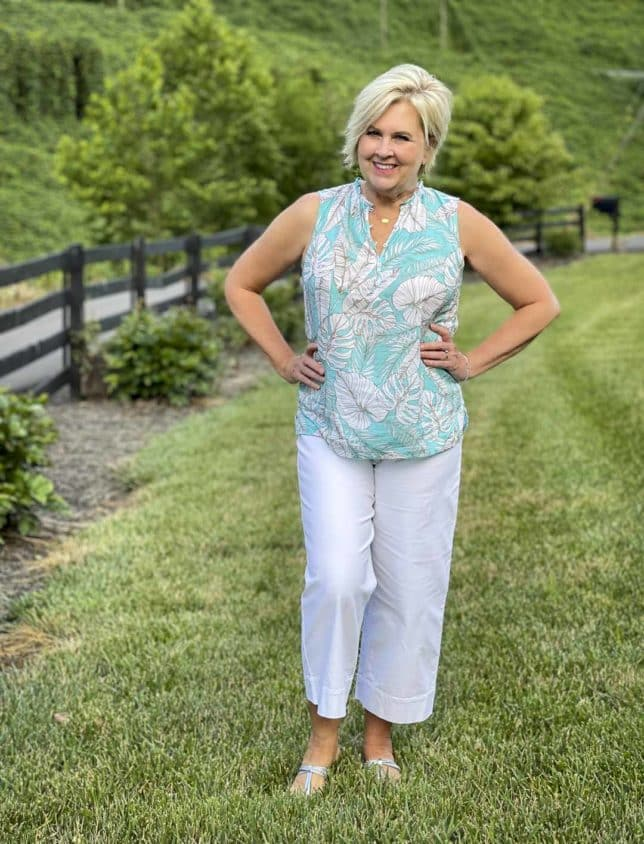 Fashion Blogger 50 Is Not Old is wearing a blue and white palm print shell with a pair of white wide leg crop pants and silver sandals from Talbots