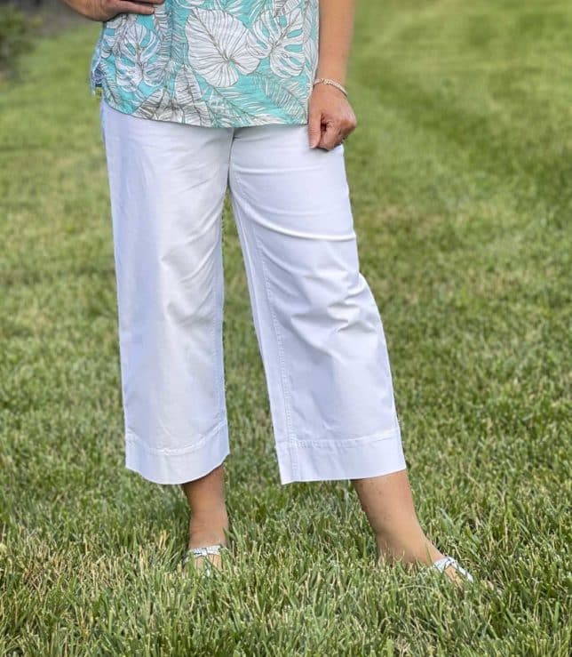 Fashion Blogger 50 Is Not Old is wearing a pair of white wide leg crop pants and silver sandals from Talbots
