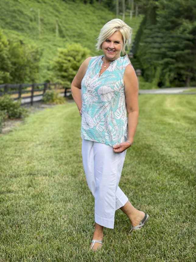 Fashion Blogger 50 Is Not Old is wearing a blue and white print shell with a pair of white wide leg crop pants and silver sandals from Talbots
