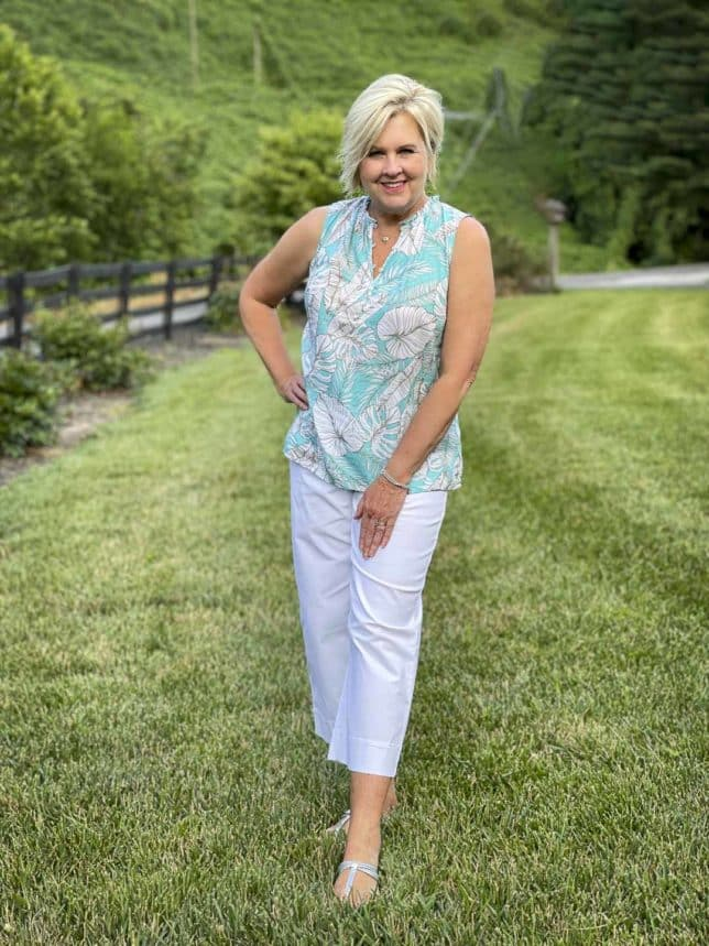 Fashion Blogger 50 Is Not Old is wearing a palm print shell with a pair of white wide leg crop pants and silver sandals from Talbots