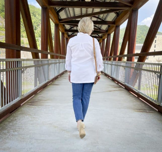 Over 40 Fashion Blogger, Tania Stephens, is walking on a bridge wearing a white button down tunic shirt, ankle length jeans, and neutral kitten heels
