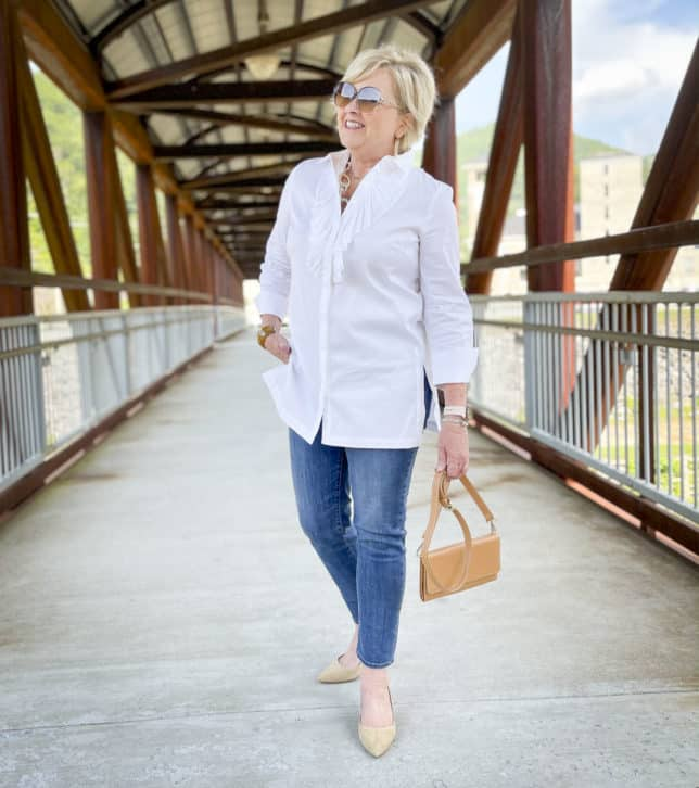 Over 40 Fashion Blogger, Tania Stephens, is wearing a white button down shirt with a large ruffle, sunglasses, ankle length jeans, and neutral kitten heels