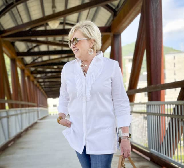Over 40 Fashion Blogger, Tania Stephens, is standing on a bridge wearing a white button down shirt with a large ruffle