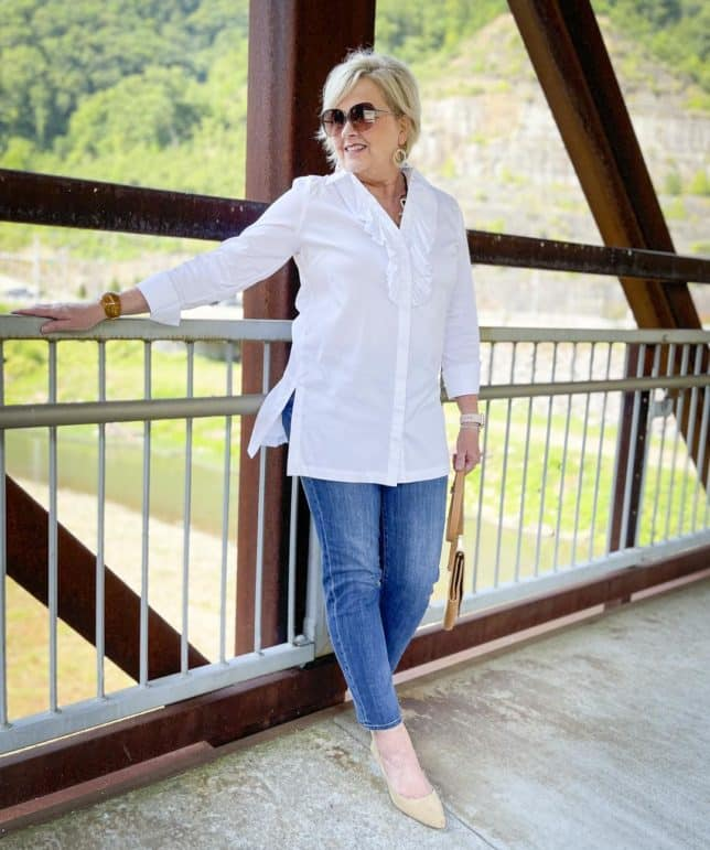 Over 40 Fashion Blogger, Tania Stephens, is wearing a white button down shirt with a large ruffle, ankle length jeans, and neutral kitten heels while standing on a bridge