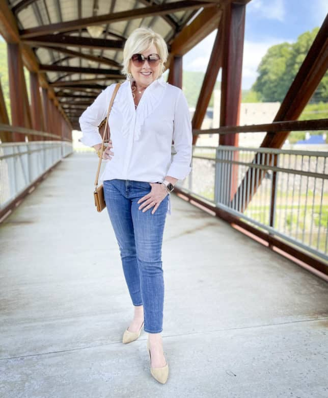 Over 40 Fashion Blogger, Tania Stephens, is on a bridge wearing a white button down shirt with a large ruffle, ankle length jeans, and neutral kitten heels