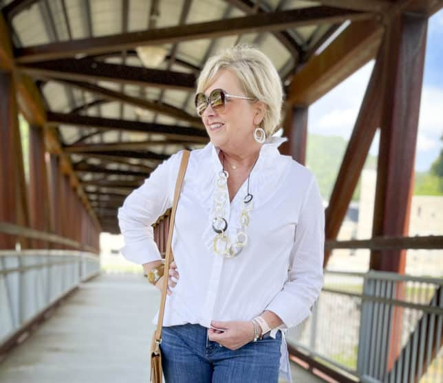 Over 40 Fashion Blogger, Tania Stephens, is wearing a white button down shirt with a large ruffle, sunglasses, a long shell necklace, and earrings