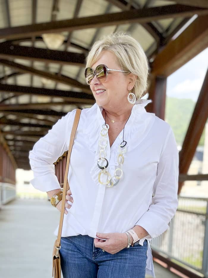 Over 40 Fashion Blogger, Tania Stephens, is wearing a white button down shirt with a large ruffle and dark sunglasses