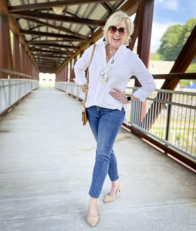 Over 40 Fashion Blogger, Tania Stephens, is laughing while wearing a white button down shirt with a large ruffle, ankle length jeans, and neutral kitten heels