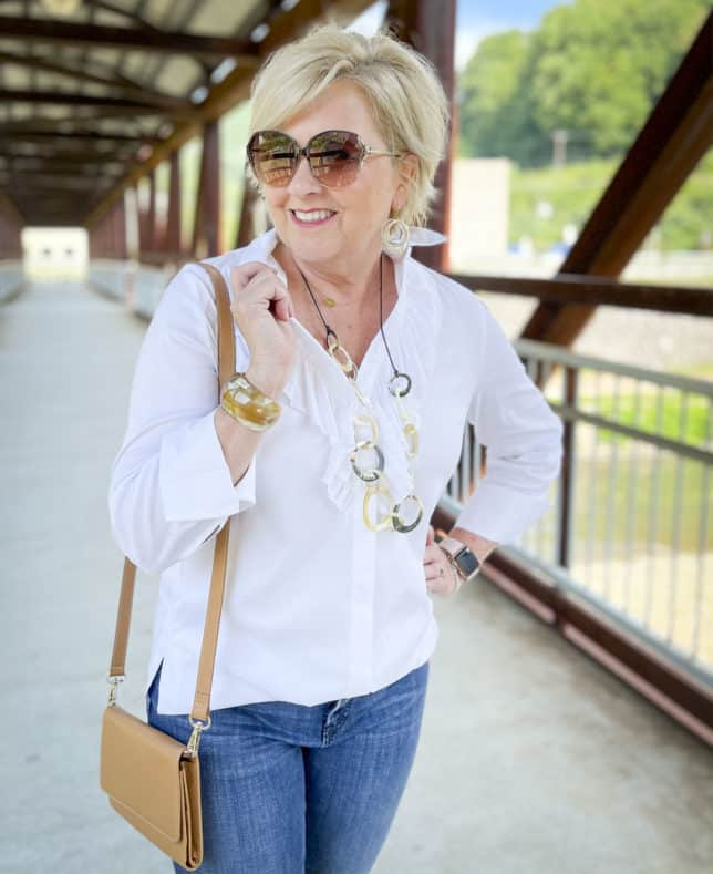 Over 40 Fashion Blogger, Tania Stephens, is wearing a white button down shirt with a large ruffle, sunglasses, a long shell necklace, and earrings from Chico's