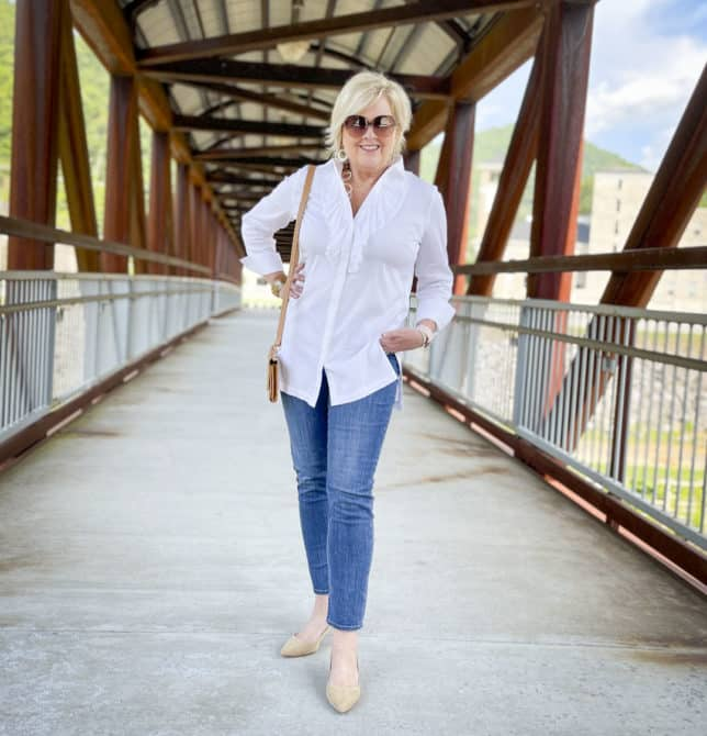 Over 40 Fashion Blogger, Tania Stephens, is wearing a white button down shirt with a large ruffle, ankle length jeans, and neutral kitten heels