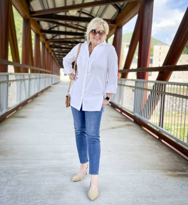 Over 40 Fashion Blogger, Tania Stephens, is in the middle of a bridge wearing a white button down shirt with a large ruffle, ankle length jeans, and neutral kitten heels