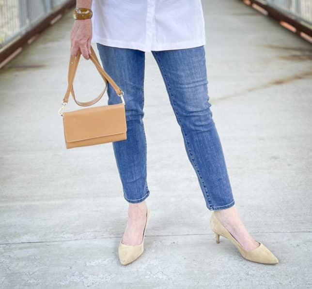 Over 40 Fashion Blogger, Tania Stephens, is wearing ankle length jeans, neutral heels, and carrying a camel crossbody wallet