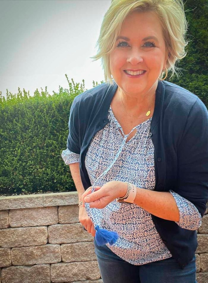 Fashion Blogger 50 Is Not Old is wearing a tasseled print top with a navy cardigan