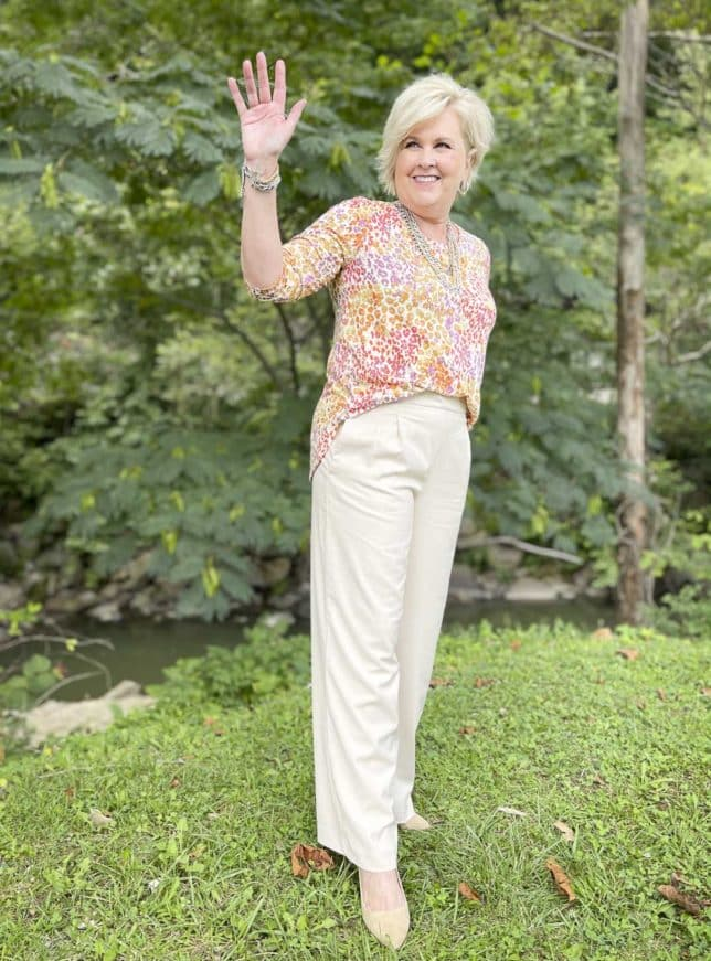 Over 40 Fashion Blogger, Tania Stephens, is waving at someone while wearing a colorful animal print tee, ecru wide leg pants, and mixed metal jewelry