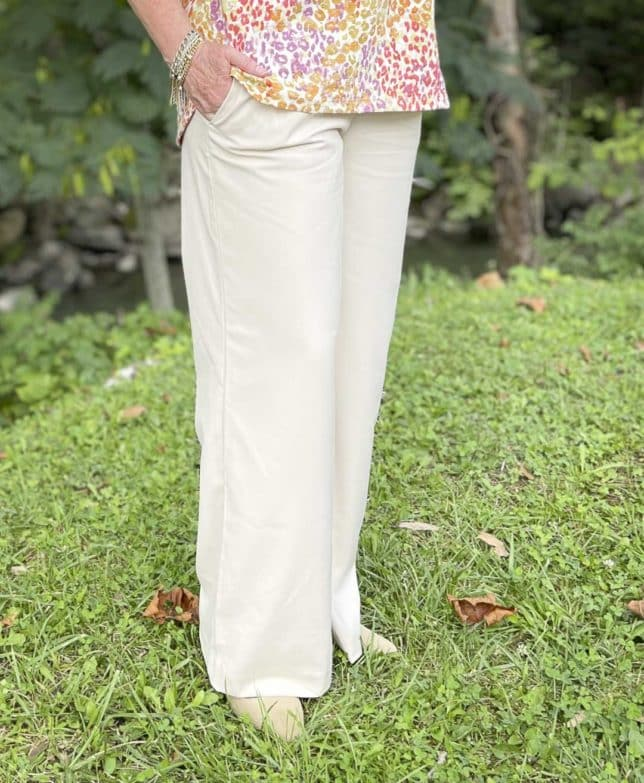 Over 40 Fashion Blogger, Tania Stephens, is wearing ecru wide leg pants and neutral flats