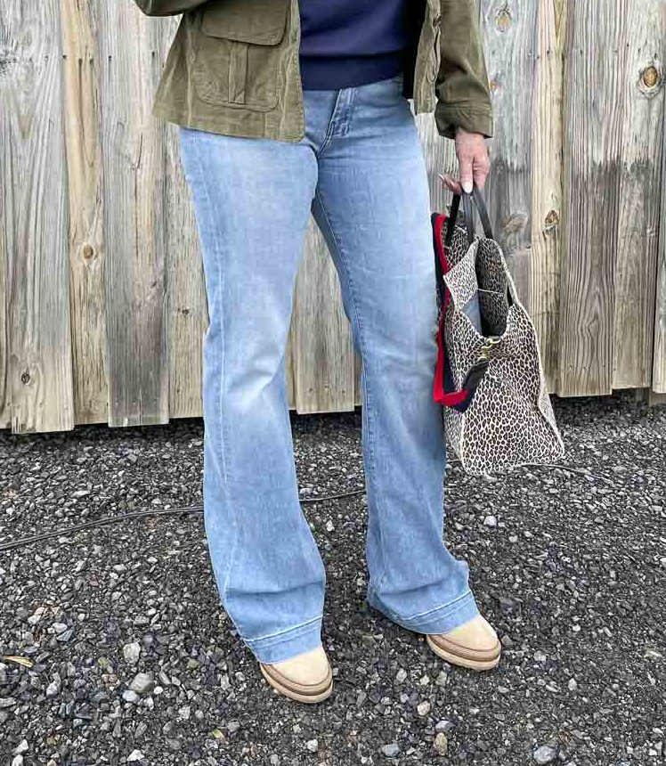 Over 40 Fashion Blogger, Tania Stephens, is wearing a pair of flare jeans and carrying a large tote bag