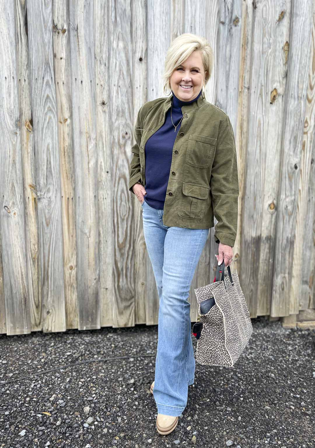 Over 40 Fashion Blogger, Tania Stephens, is wearing a olive thin wale corduroy jacket, a navy turtleneck sweater, and a pair of flare jeans and carrying a large tote bag