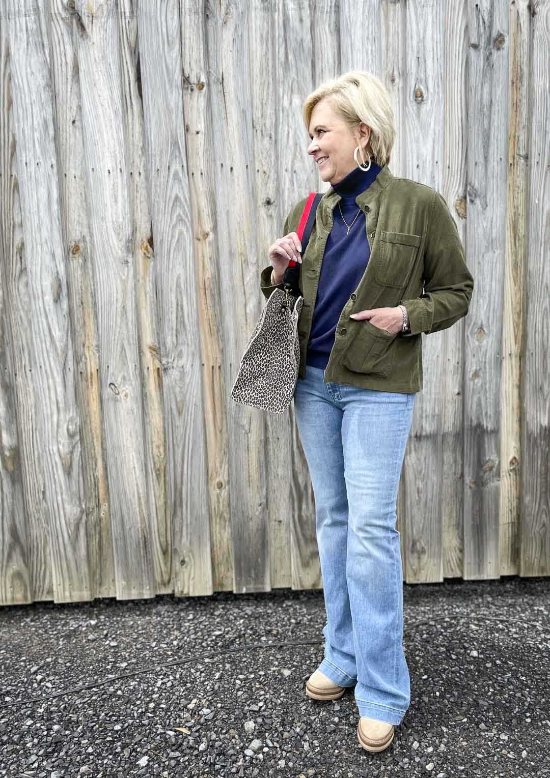 Over 40 Fashion Blogger, Tania Stephens, is wearing a olive thin wale corduroy jacket, a turtleneck sweater, and a pair of flare jeans and carrying a large tote bag