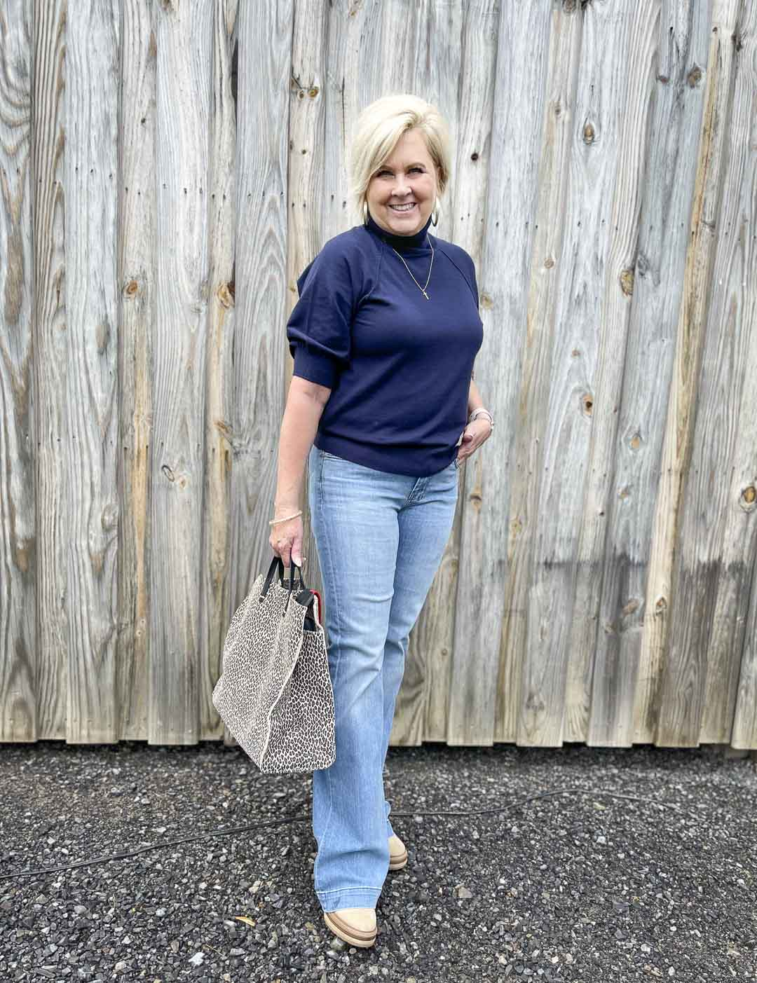 Over 40 Fashion Blogger, Tania Stephens, is wearing a navy puff sleeve turtleneck sweater with a pair of flare jeans and carrying a large tote bag