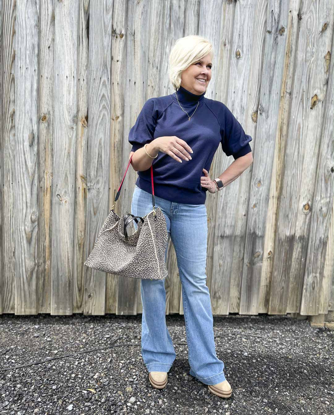 Over 40 Fashion Blogger, Tania Stephens, is wearing a navy turtleneck sweater with a pair of flare jeans and carrying a large tote bag