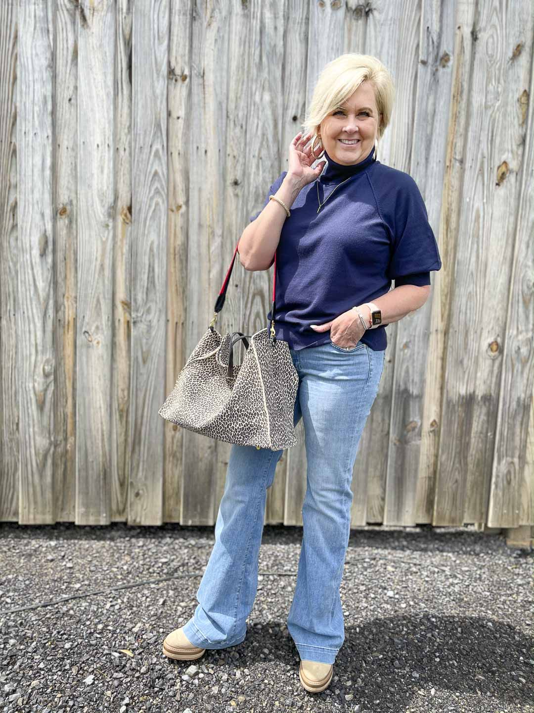 Over 40 Fashion Blogger, Tania Stephens, is wearing a navy turtleneck sweater, a pair of flare jeans, and carrying a large tote bag