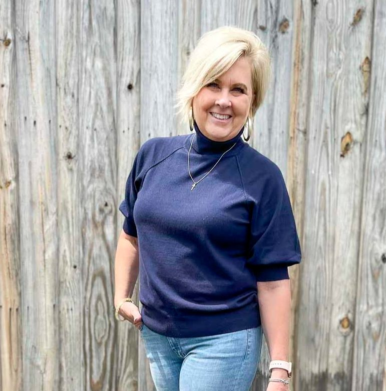Over 40 Fashion Blogger, Tania Stephens, is wearing a navy puff sleeve turtleneck sweater