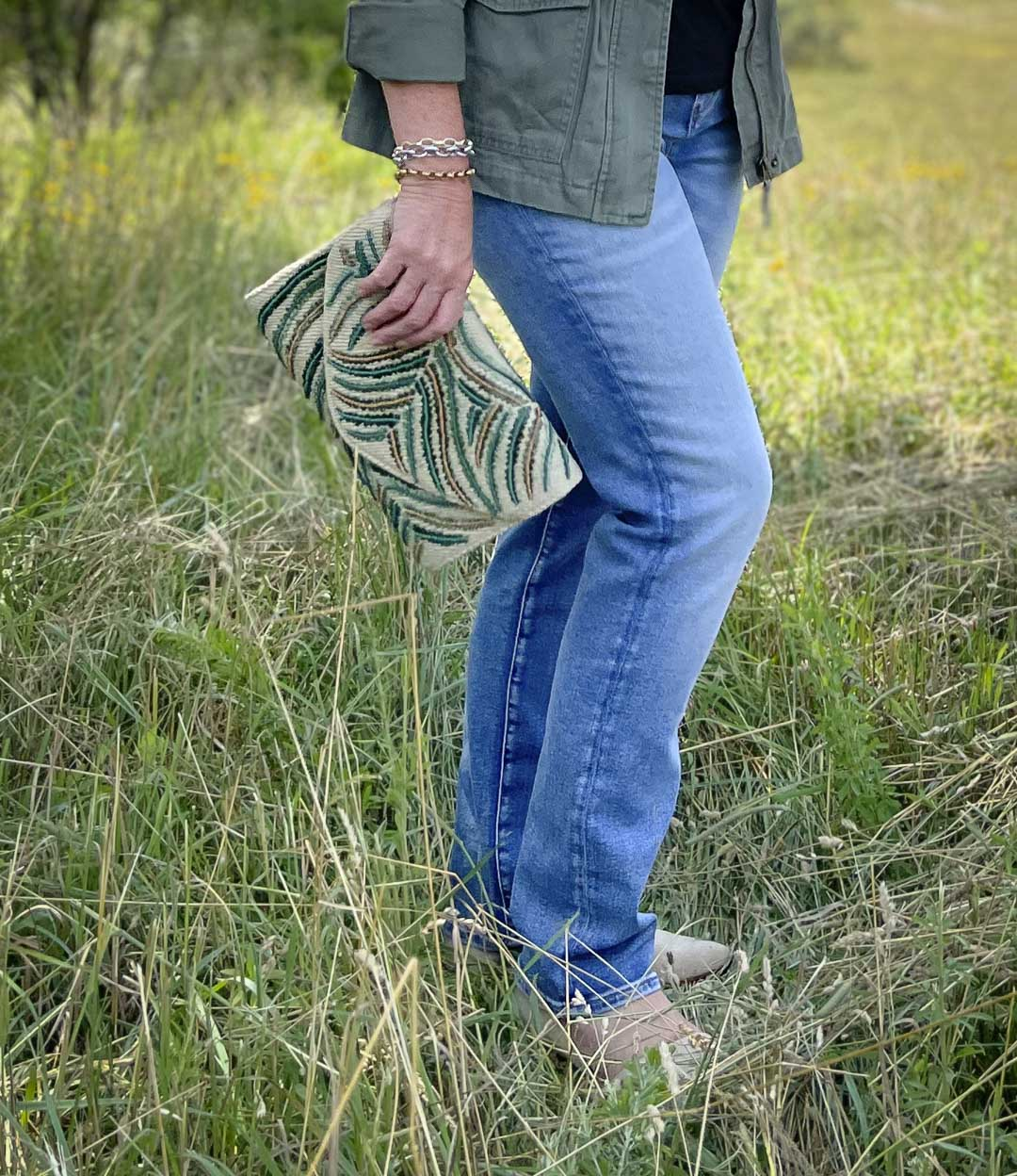 Fashion Blogger 50 Is Not Old is wearing jeans and an embroidered clutch