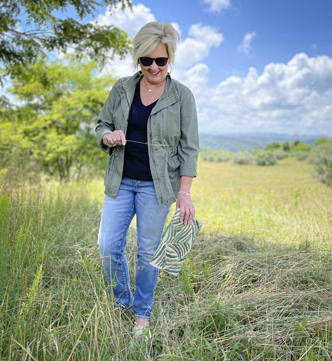 Fashion Blogger 50 Is Not Old is standing in a field while wearing black and olive together with jeans and an embroidered clutch