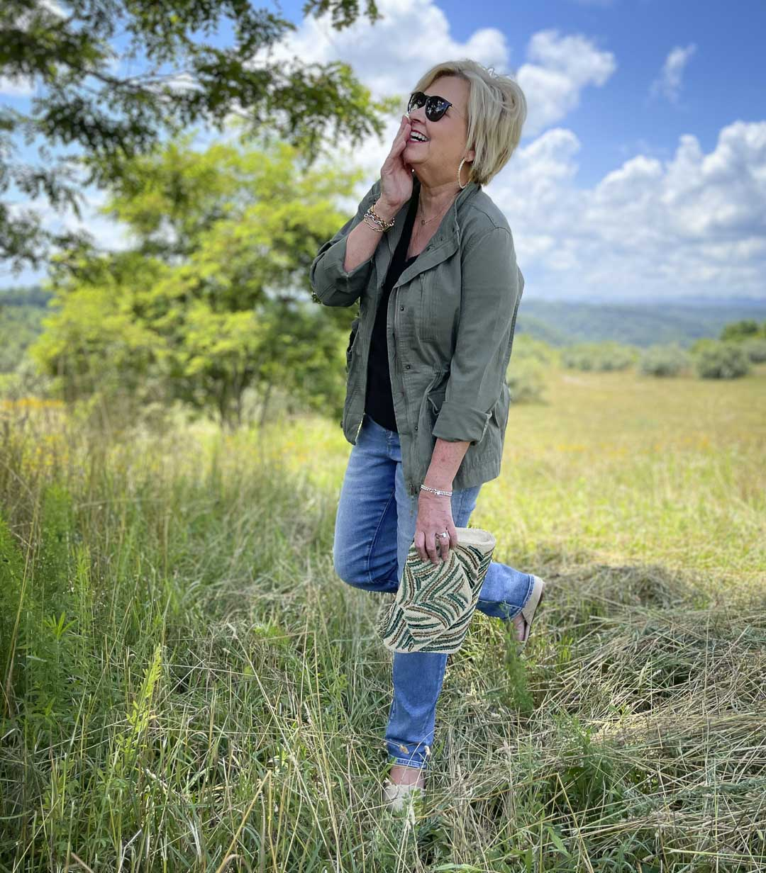 Fashion Blogger 50 Is Not Old is laughing while wearing black and olive together with jeans and an embroidered clutch