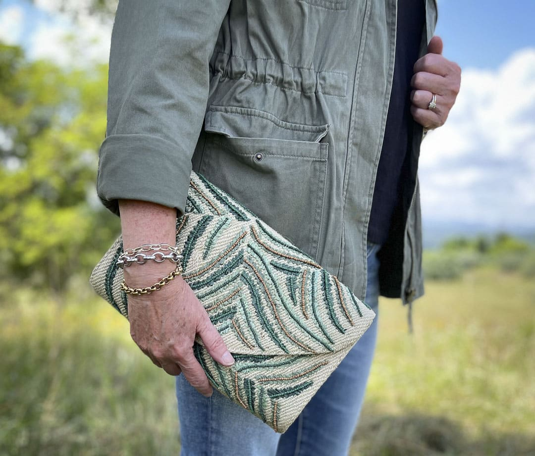 Fashion Blogger 50 Is Not Old is carrying an embroidered clutch in olive and khaki