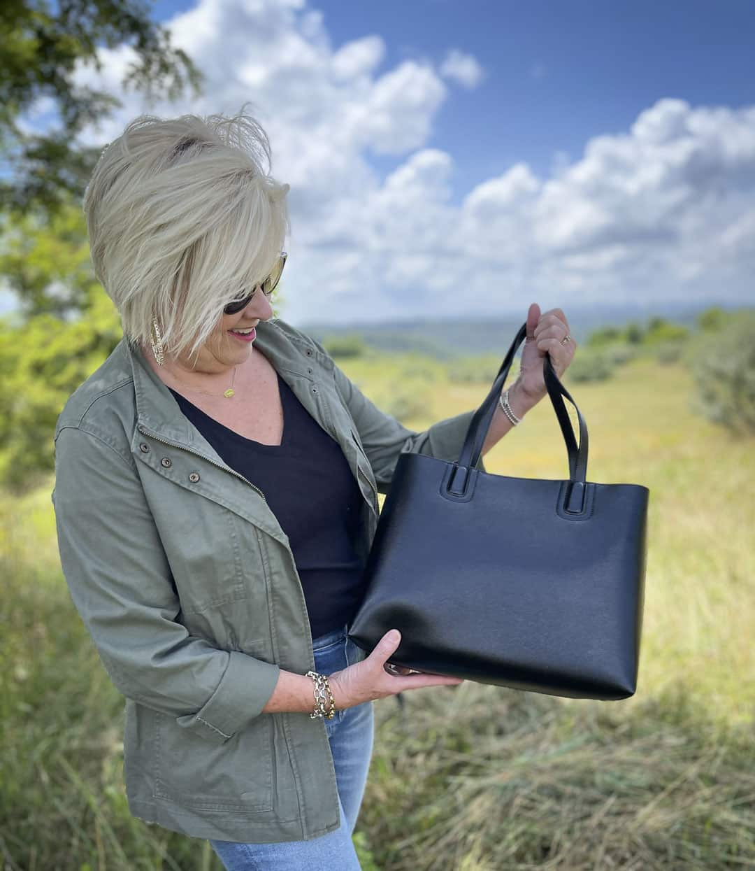 Fashion Blogger 50 Is Not Old is showing a black tote that she is carrying with an olive jacket