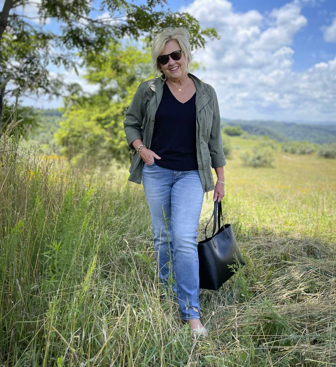 Fashion Blogger 50 Is Not Old is in a field wearing black and olive together with jeans and a black leather tote