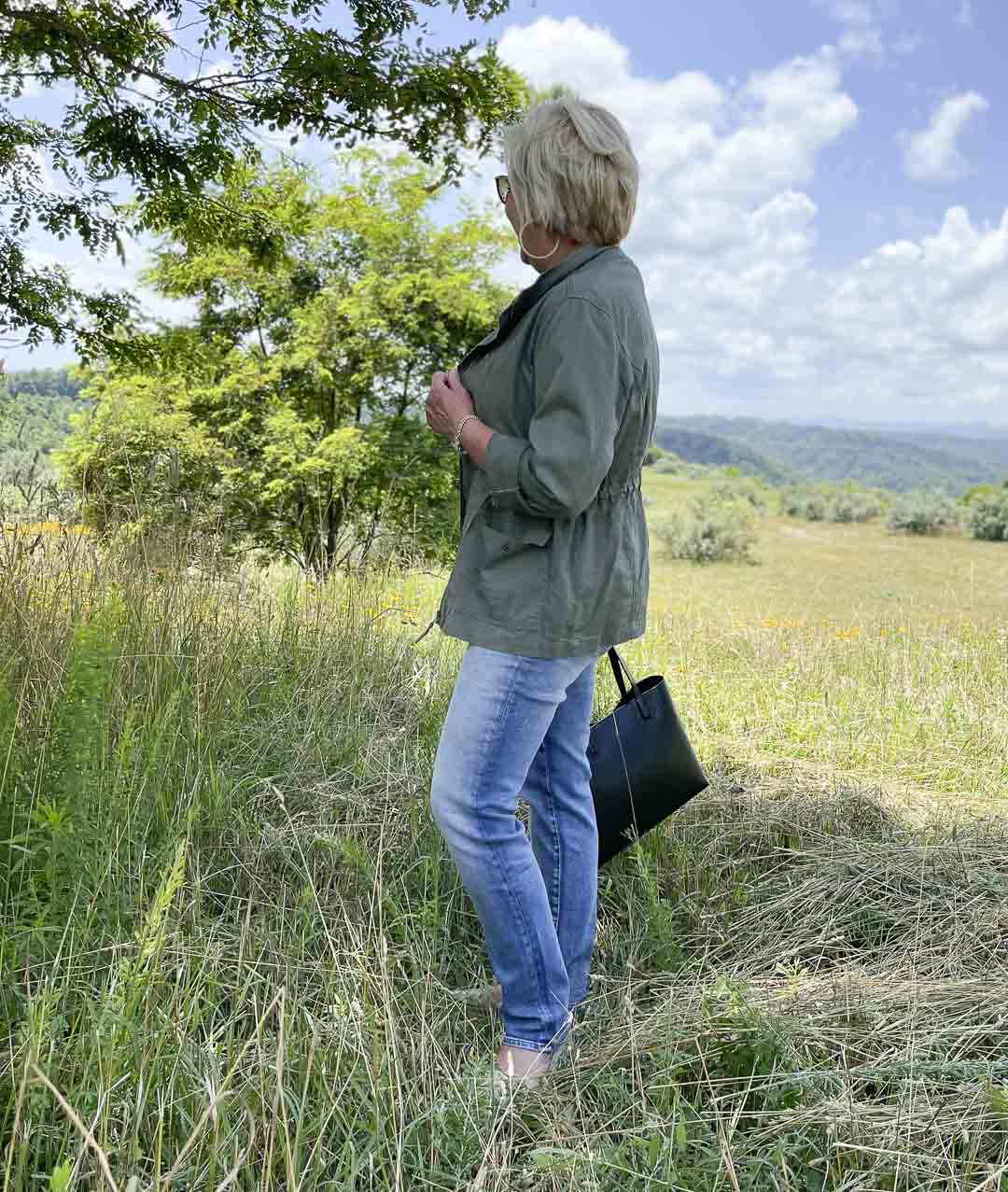Fashion Blogger 50 Is Not Old is standing in a field wearing an olive jacket with jeans and a black tote