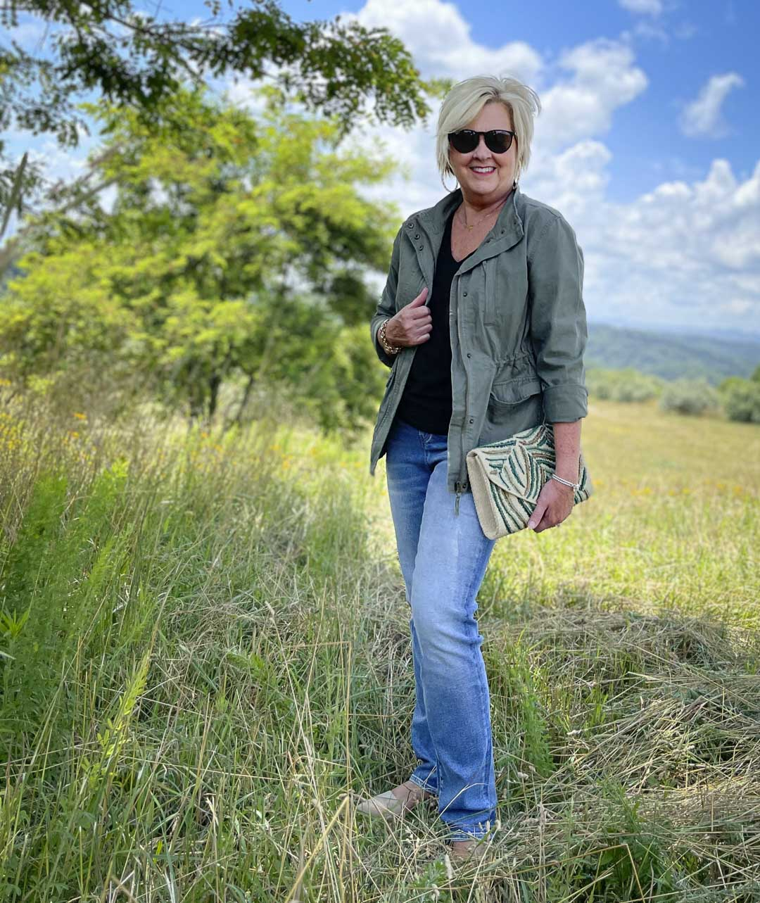 Fashion Blogger 50 Is Not Old is wearing black and olive together with jeans, Ray-Ban sunglasses, and an embroidered clutch