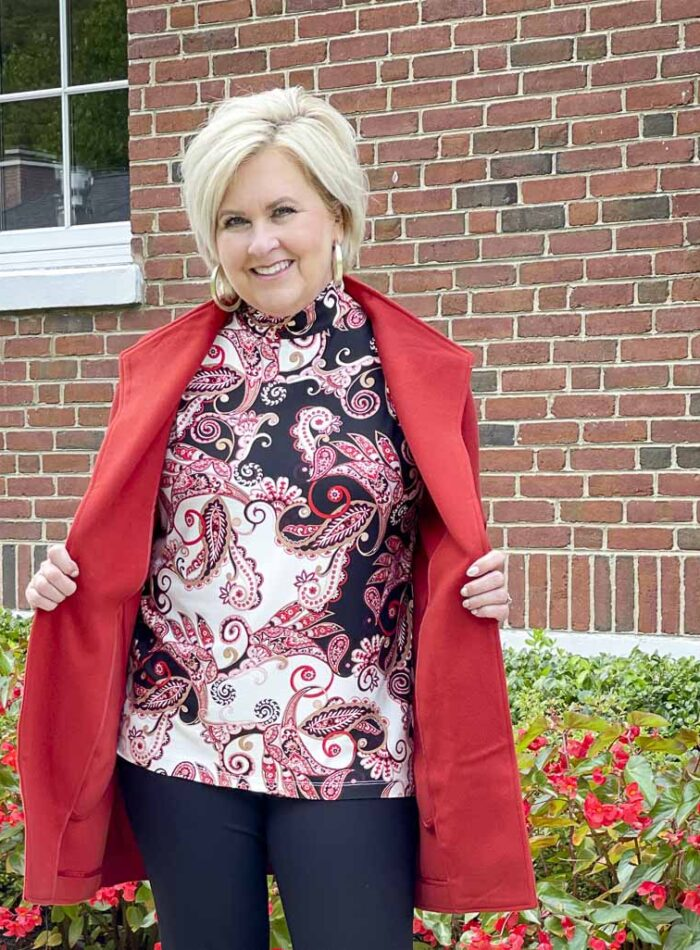 Over 40 Fashion Blogger, Tania Stephens, is wearing a red sweater jacket with a paisley top