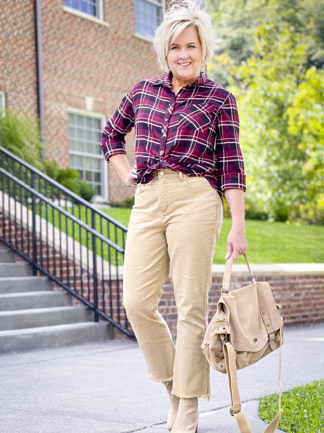 Over 40 Fashion Blogger, Tania Stephens is wearing a wine plaid flannel shirt tied at the waist with crop jeans to show how to get the most out of your wardrobe