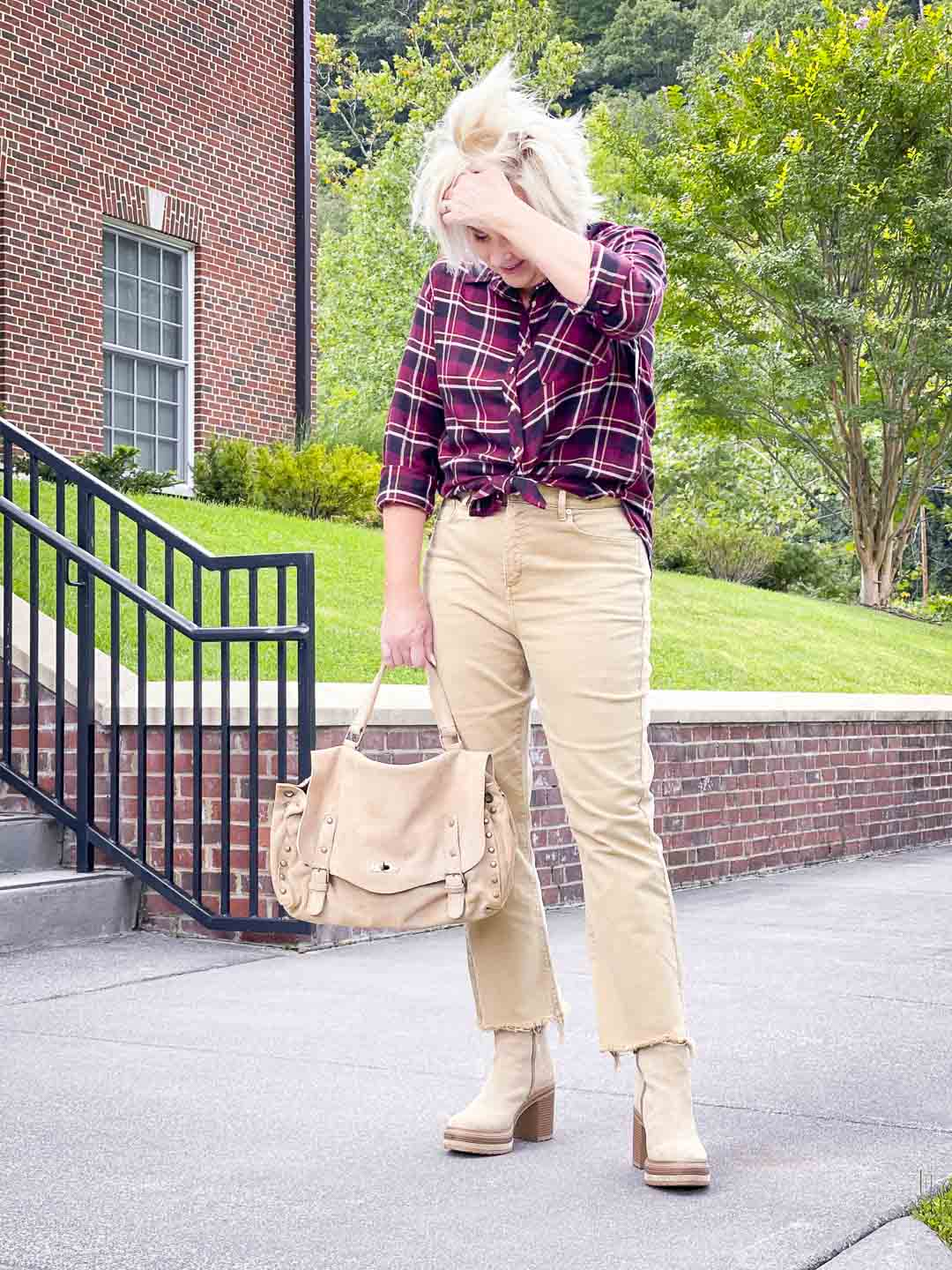 Over 40 Fashion Blogger, Tania Stephens's hair is flying everywhere while she is wearing a plaid flannel shirt with crop jeans