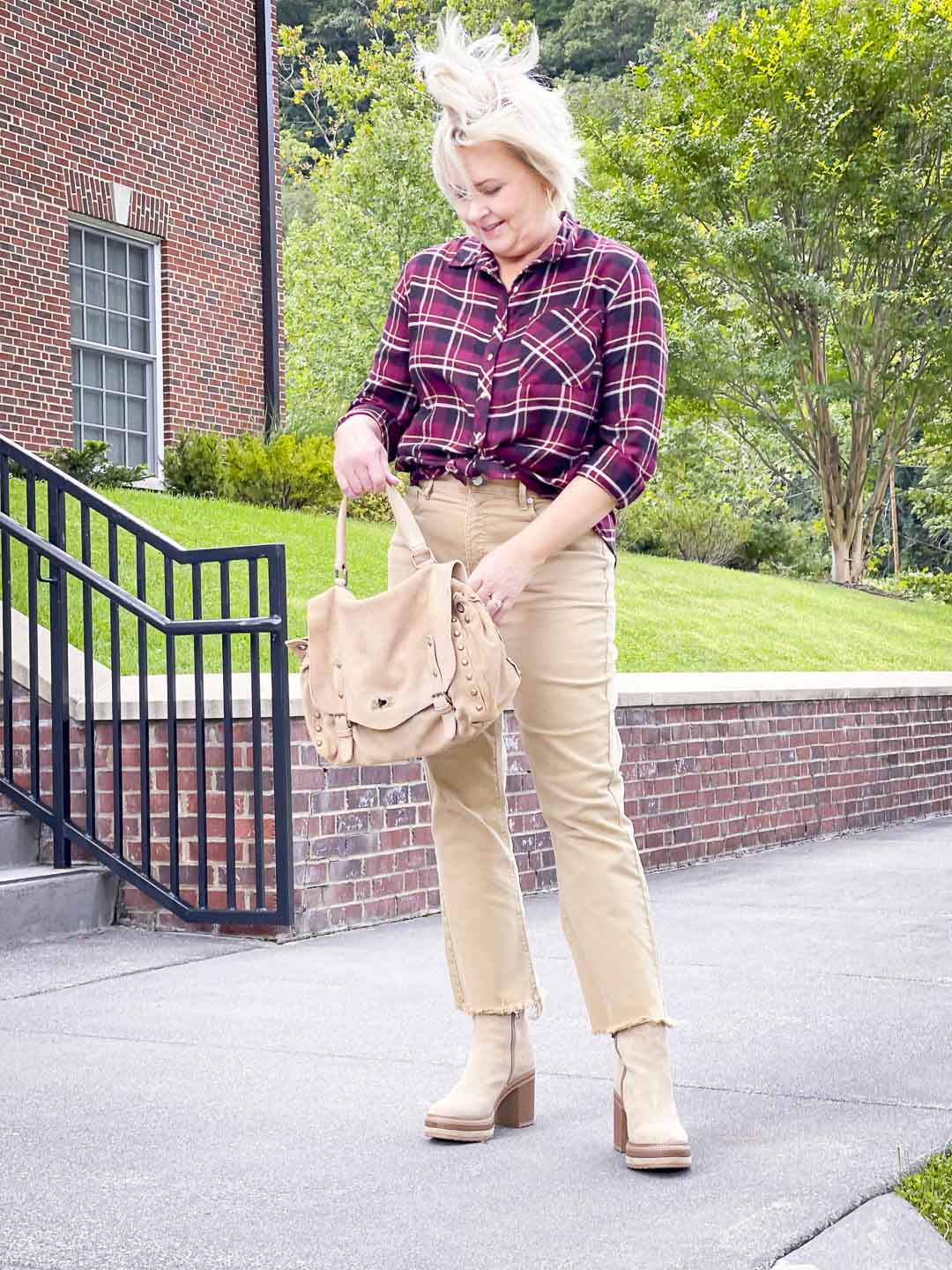 Over 40 Fashion Blogger, Tania Stephens's hair is being blown by the wind while wearing a plaid flannel shirt with crop jeans to sho how to get the most out of your wardrobe
