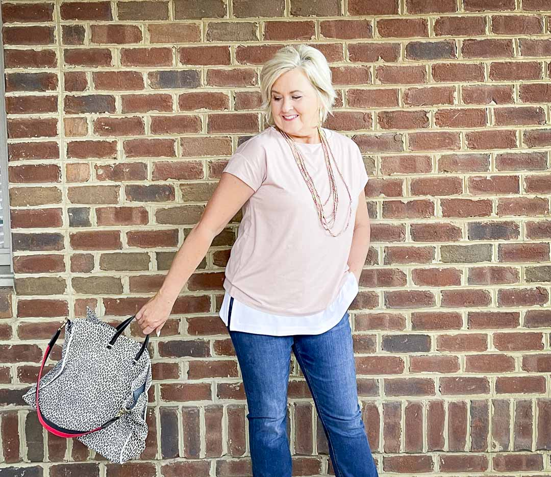 Over 40 Fashion Blogger, Tania Stephens, is dressed in blush pink, a white tank top, bootcut jeans, and carrying a suede animal print tote
