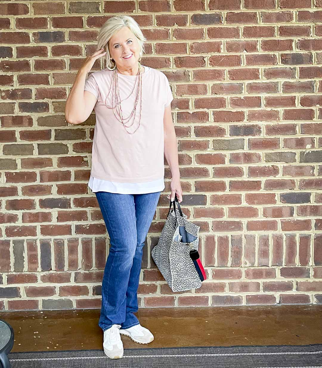 Over 40 Fashion Blogger, Tania Stephens, is dressed in blush pink, a white tank tunic, slim bootcut jeans, and carrying a suede animal print tote
