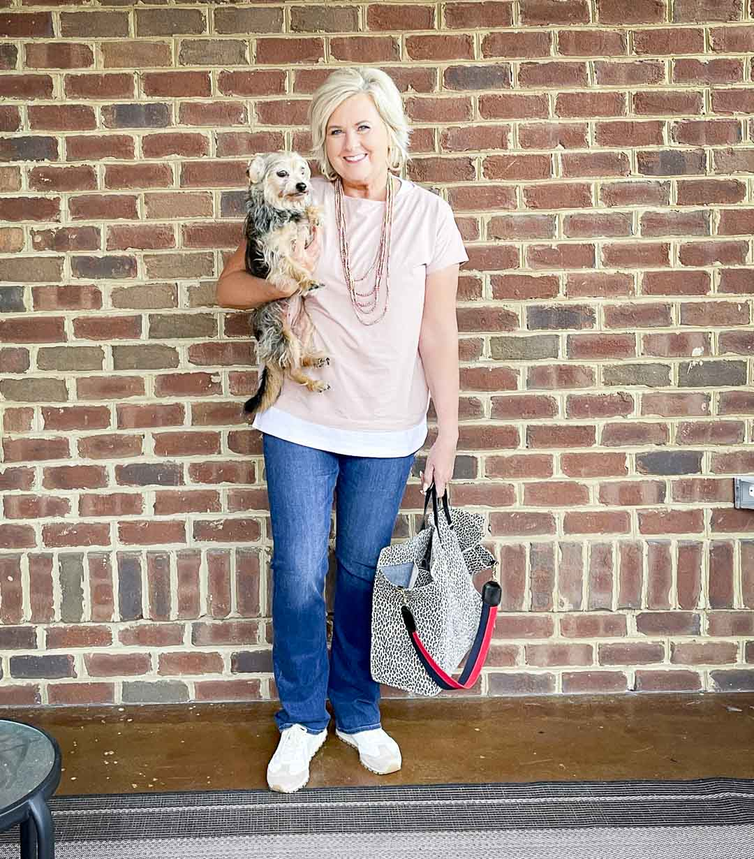 Over 40 Fashion Blogger, Tania Stephens, is dressed in blush pink, a white tank tunic, bootcut jeans, and carrying a suede animal print tote